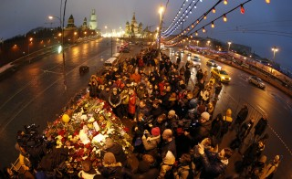 People gather at the site where Boris Nemtsov was recently murdered, with St. Basil's Cathedral and the Kremlin walls seen in the background, in central Moscow, February 28, 2015. The murder of Nemtsov drew condemnation on Saturday from leaders and politicians around the world, who paid tribute to the outspoken critic of President Vladimir Putin and Russia's role in the Ukraine crisis. Picture taken with fish eye lens. REUTERS/Maxim Zmeyev (RUSSIA - Tags: POLITICS CRIME LAW CITYSCAPE) - RTR4RJQW