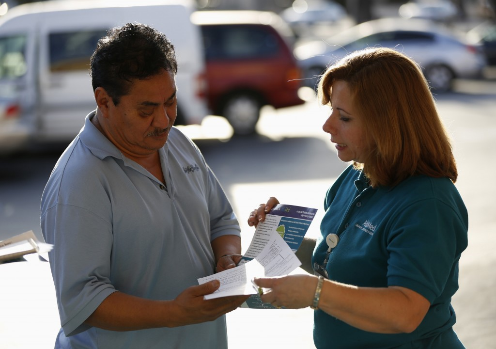 Engrith Acosta, patient care coordinator at AltaMed, speaks to a man during a community outreach on Obamacare in Los Angeles, California November 6, 2013. Concerns among Hispanics that signing up for medical insurance under President Barack Obama's healthcare law may draw the scrutiny of immigration authorities has hurt enrollment, according to advocates of the policy. Photo by Mario Anzuoni/Reuters