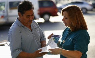 Engrith Acosta, patient care coordinator at AltaMed, speaks to a man during a community outreach on Obamacare in Los Angeles, California November 6, 2013. Questions on challengers' legal rights is unlikely to derail Supreme Court's decision on health care tax subsidies. Photo by Mario Anzuoni/Reuters