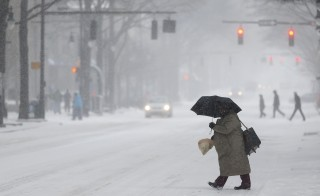 A woman crosses a street as snow falls in Charlotte, North Carolina February 12, 2014. This February has been the coldest ever recorded in many US cities. Photo by Chris Keane/REUTERS.