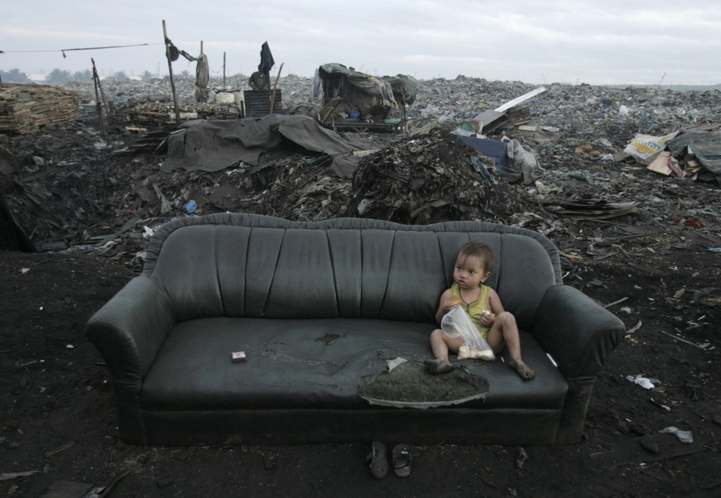 A child eats breakfast in a garbage dump, where hundreds of people live and make a living by recycling waste and making charcoal, in the Tondo section of Manila December 9, 2007. Photo by Darren Whiteside/Reuters