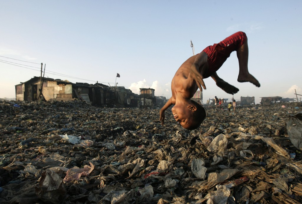 A boy plays at a garbage dump where hundreds of people stay and make a living out of recycling waste and making charcoal in Tondo, Manila in 2007. Photo by Darren Whiteside/Reuters