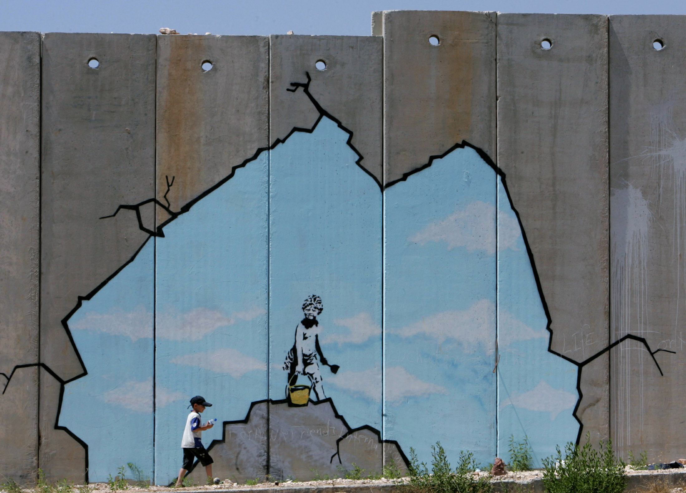 A Palestinian boy walks past a drawing by British graffiti artist Banksy, along part of the controversial Israeli barrier near the Kalandia checkpoint in the West Bank August 10, 2005. Photo by Ammar Awad/REUTERS.