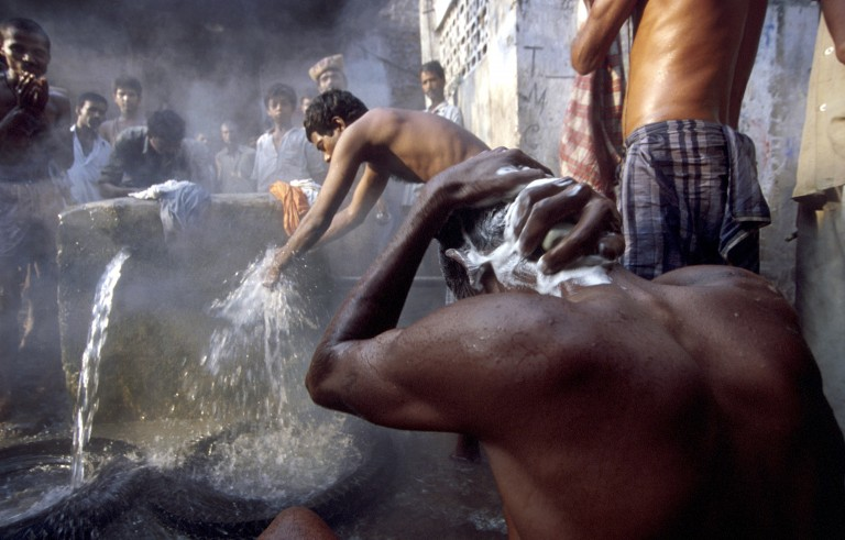Indian men bathing on the streets of Calcutta at dawn, 2000. Photo by Lynsey Addario