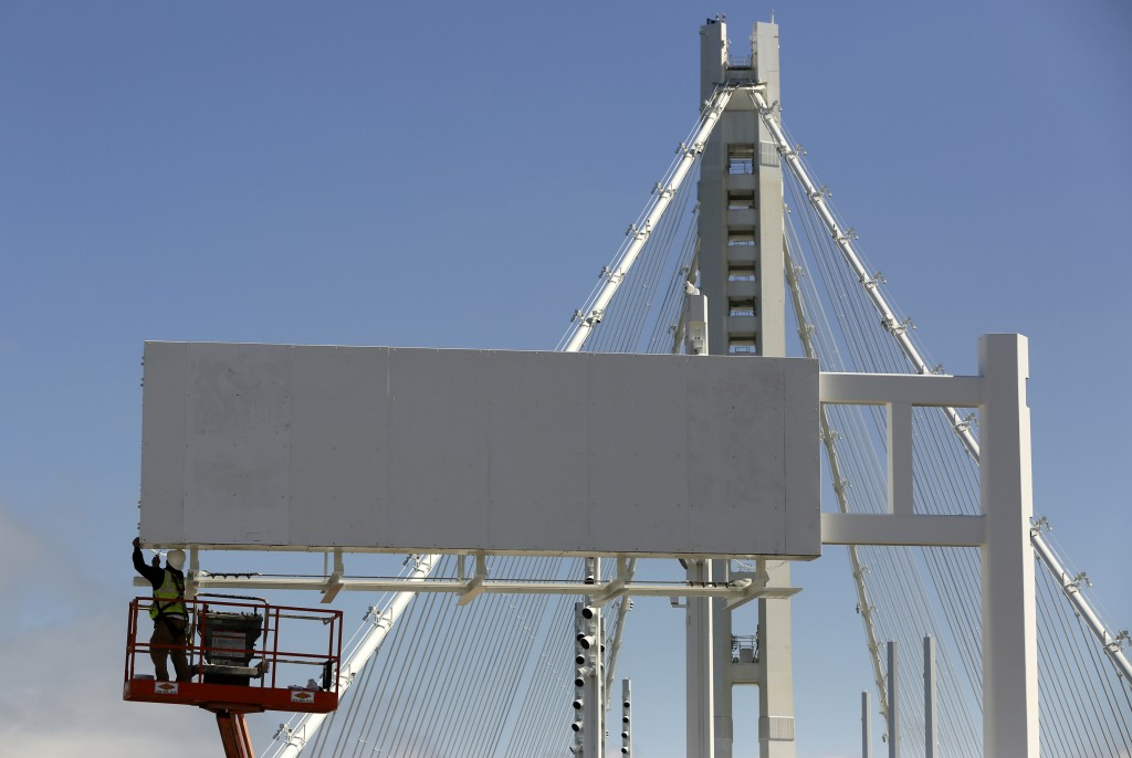 Photo by Robert Galbraith/Reuters. A worker installs a sign on the new span of the Bay Bridge, San Francisco, California August 26, 2013. The President's budget would tax U.S. companies' foreign profits to fund bridge upgrades and other public works projects.
