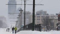 Pedestrians walk along snow covered, MBTA subway rails on Commonwealth Avenue in Boston
