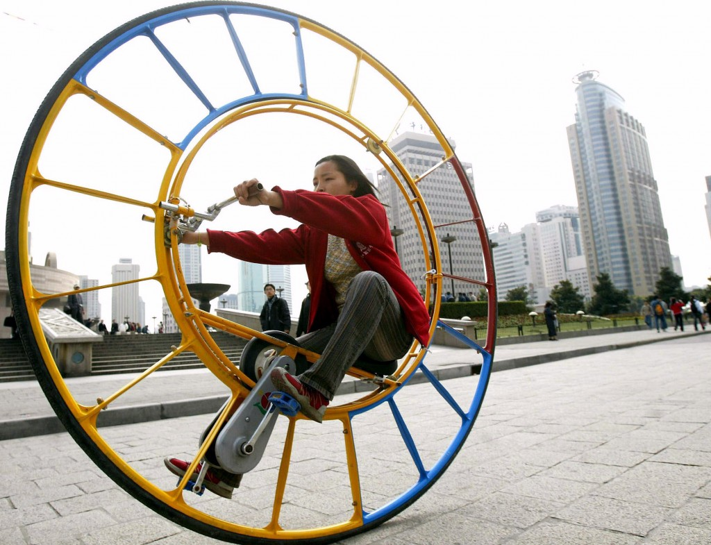 A woman pedals a unicycle that resembles a human hamster wheel at a park in Shanghai. This unicycle's inventor Li Yongli called it