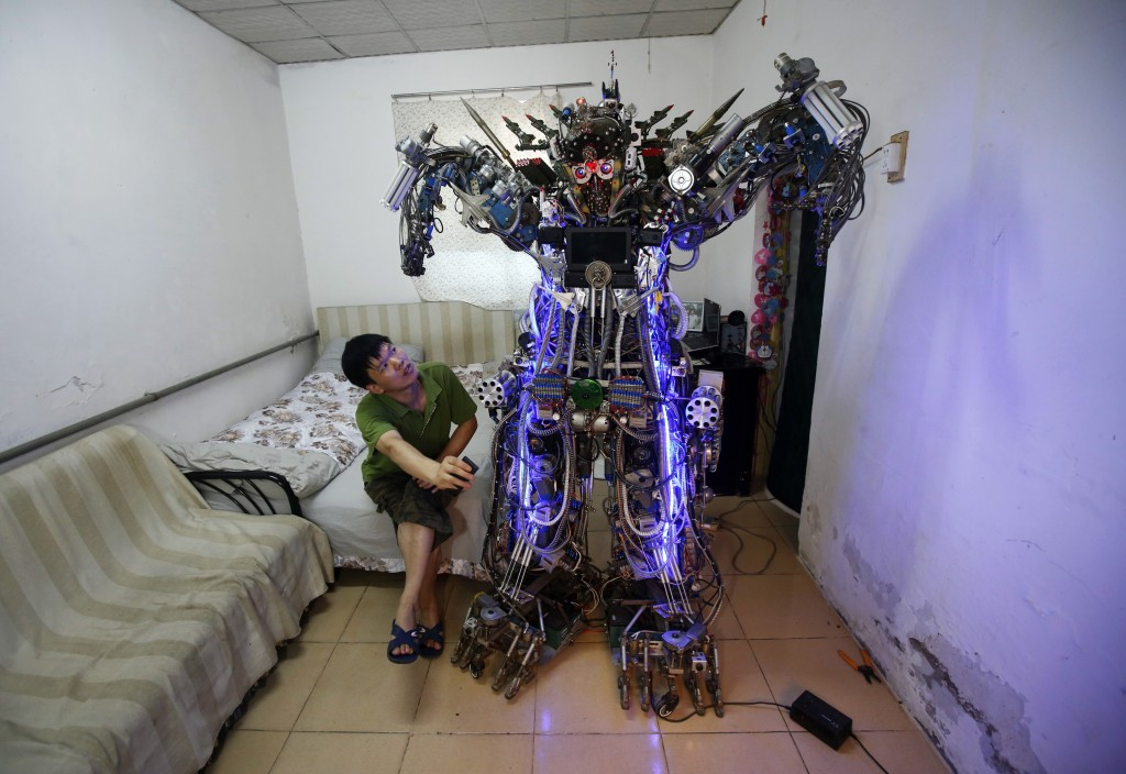 Chinese inventor Tao Xiangli uses a remote control to give commands to the robot, which he built out of scrap metal and wires and named
