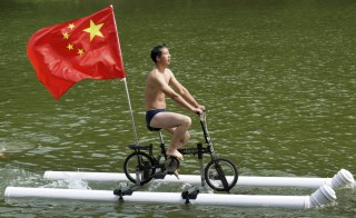 A Chinese flag is seen as Liu Wanyong performs on his invention, an improvised bicycle which is held afloat by plastic tubes, in Zhenning, Guizhou province. Liu, 52, is a grassroots inventor who mostly creates things that are related with the traditional village lives of the ethnic minority people in Guizhou. Photo by Reuters/Stringer.