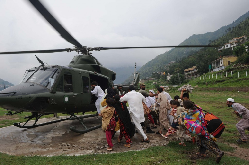 Evacuating Floods survivors swarm an army helicopter to evacuate a town in Swat valley after flooding. AFP/Getty