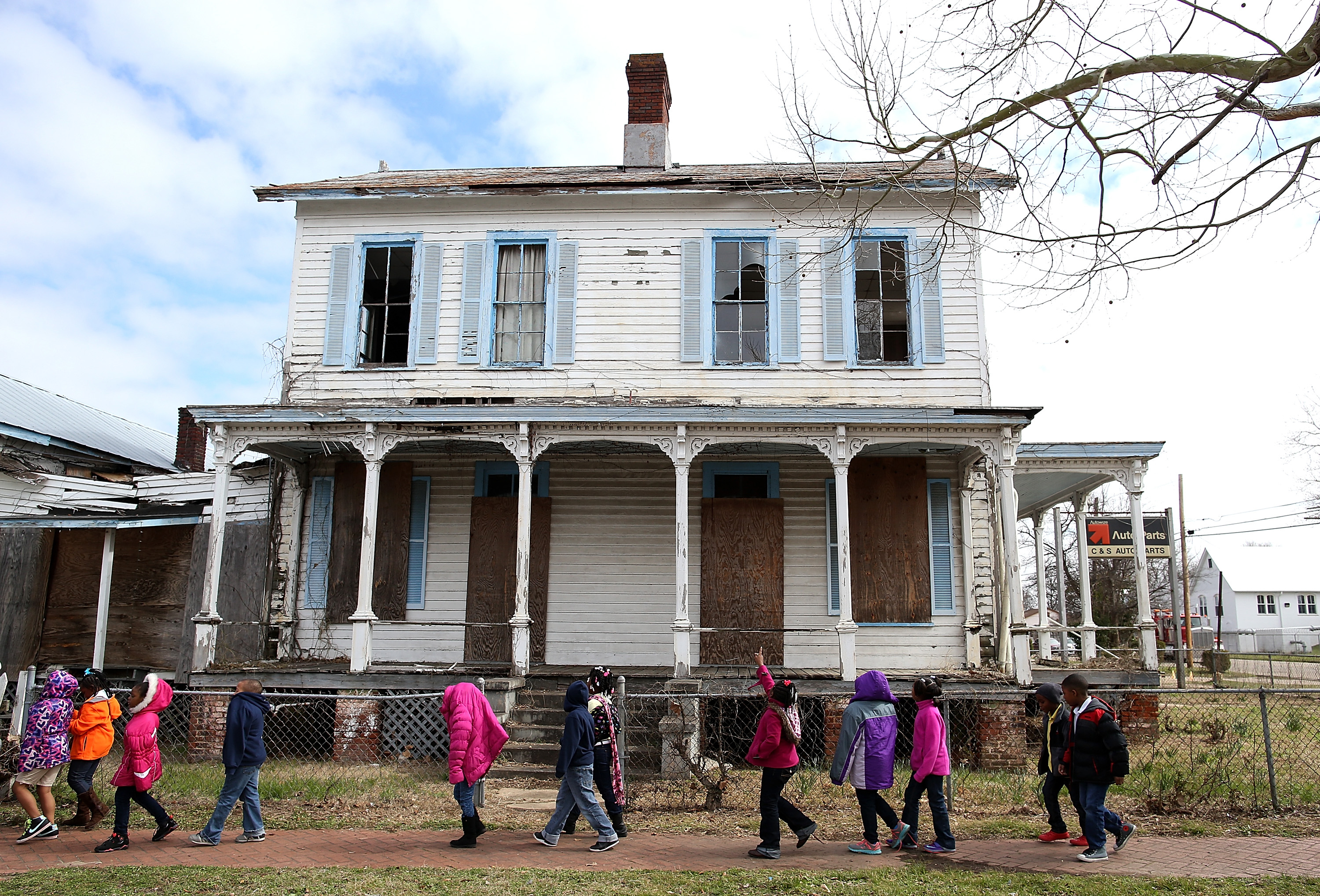 SELMA, AL - MARCH 06: School kids walk by a vacant home that is along the historic route that civil rights marchers took during the Selma to Montgomery march on March 6, 2015 in Selma, Alabama. 50 years after the historic civil rights march from Selma to Montgomery where marchers were beaten by State police officers as they crossed the Edmund Pettus Bridge, Selma struggles economically and is one of the poorest cities in Alabama with a 10.2 percent unemployment rate and over 40 percent of residents living below the national poverty level. (Photo by Justin Sullivan/Getty Images)