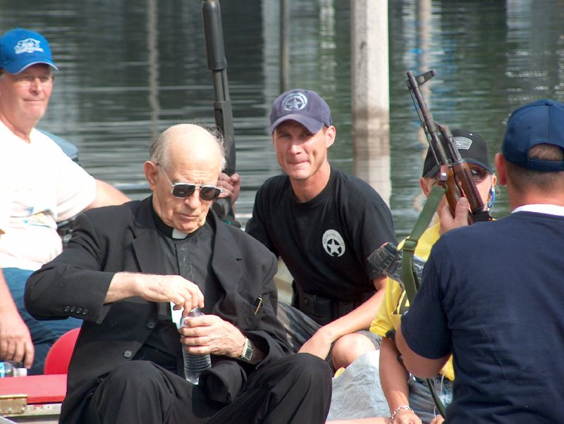"Father Miguel Father Miguel, a Catholic priest who served at Charity for what Bryant-Penland says is ""as long as I can remember,"" being evacuated by a Wildlife and Fisheries airboat. -- Photo by Mooney Bryant-Penland"