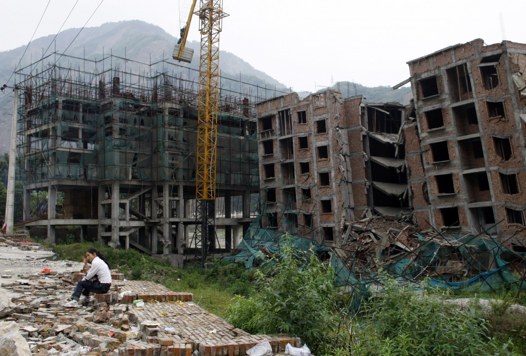 New Buildings Rise A woman mourns her deceased relatives at the devastated town of Beichuan on May 12, 2009, one year after the earthquake hit. The destruction wiped out many businesses, but has created thousands of construction jobs for Chinese laborers. (China Photos/Getty Images)