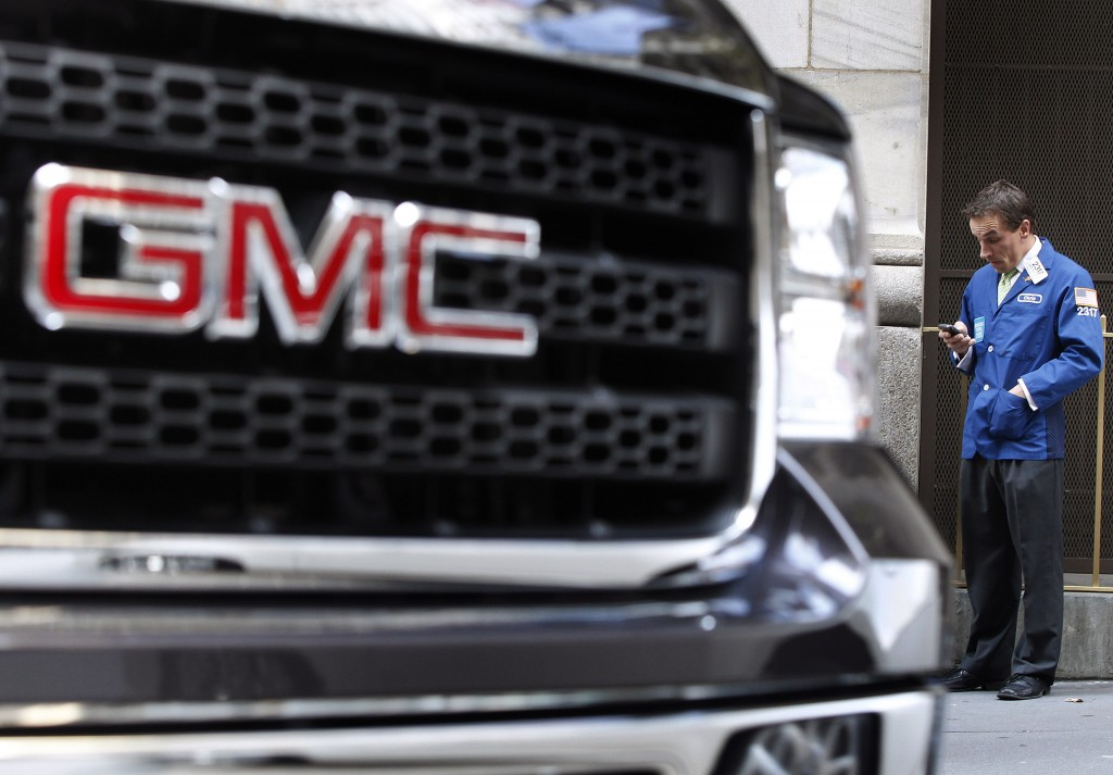 A GMC vehicle is seen parked in front of a trader standing outside of the New York Stock Exchange on Nov. 18, 2010. On Monday, GM announced a $5 billion stock buyback, part of bigger trend in corporate America, argues entrepreneur Nick Hanauer, that's threatening the American economy. Photo by REUTERS/Shannon Stapleton.