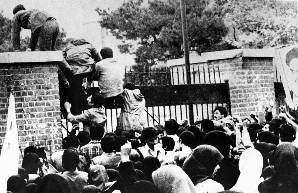 iranian students climb over the wall of the u s emby in tehran during the iranian revolution