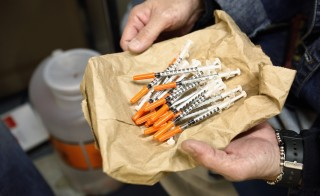 A woman shows her clean syringes at the Aids Center of Queens County needle exchange outreach center in New York in 2006. Indiana Governor Mike Pence has launched a 30-day needle-exchange program to stop the virus, which officials say is being spread by addicts sharing infected needles. Credit: REUTERS/Shannon Stapleton