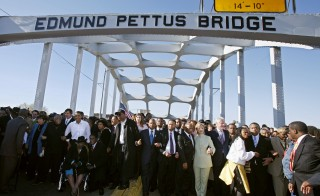 Then-presidential candidates Senators Barack Obama (L in white) and Hillary Clinton (R in green outfit) cross the Edmond Pettus Bridge during a re-enactment of the 1965 Selma to Montgomery march in Selma, Alabama, March 4, 2007. The Bloody Sunday commemoration continued Sunday, March 8, 2015 with gatherings and other events in Selma. Photo by Lee Celano/Reuters