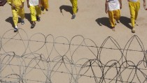 Detainees pass the time as they seen behind wire at Camp Bucca in southern Iraq