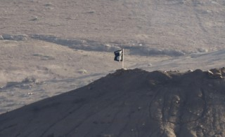 A black flag belonging to the Islamic State is seen near the Syrian town of Kobani, as pictured from the Turkish-Syrian border near the southeastern town of Suruc in Sanliurfa province, October 6, 2014. Islamic State militants raised their flag on a building on the eastern outskirts of the Syrian border town of Kobani on Monday after an assault of almost three weeks, but the town's Kurdish defenders said they had not reached the city centre. A black flag belonging to Islamic State was visible from across the Turkish border atop a four-storey building close to the scene of some of the most intense clashes in recent days. Photo by REUTERS/Umit Bektas .