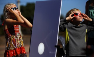 A reflected image of the sun is seen on a white board as kids look up to view the beginning a partial solar eclipse in San Diego, California, Oct. 23, 2014. A total solar eclipse will take place on Friday, but only Europe and parts of Asian and African will be able to view it. Photo by Mike Blake/Reuters