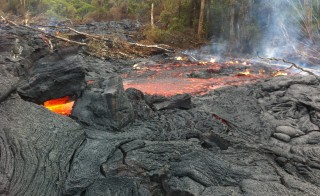 The lava flow from the Kilauea Volcano is seen downslope of the house that burned on November 10 in this U.S. Geological Survey (USGS) handout photo taken near the village of Pahoa, Hawaii, November 13, 2014.  The slow-moving lava flow continues to move near a transfer station at an industrial complex on Thursday, three days after the flow destroyed its first home. Picture taken November 13, 2014. REUTERS/USGS/Handout via Reuters (UNITED STATES - Tags: ENVIRONMENT DISASTER) THIS IMAGE HAS BEEN SUPPLIED BY A THIRD PARTY. IT IS DISTRIBUTED, EXACTLY AS RECEIVED BY REUTERS, AS A SERVICE TO CLIENTS. FOR EDITORIAL USE ONLY. NOT FOR SALE FOR MARKETING OR ADVERTISING CAMPAIGNS - RTR4E6NV