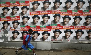 A schoolgirl walks past campaign posters in support of Nigeria's President Goodluck Jonathan along a road in Ikoyi district in Lagos February 13, 2015. Photo by Akintunde Akinleye/Reuters