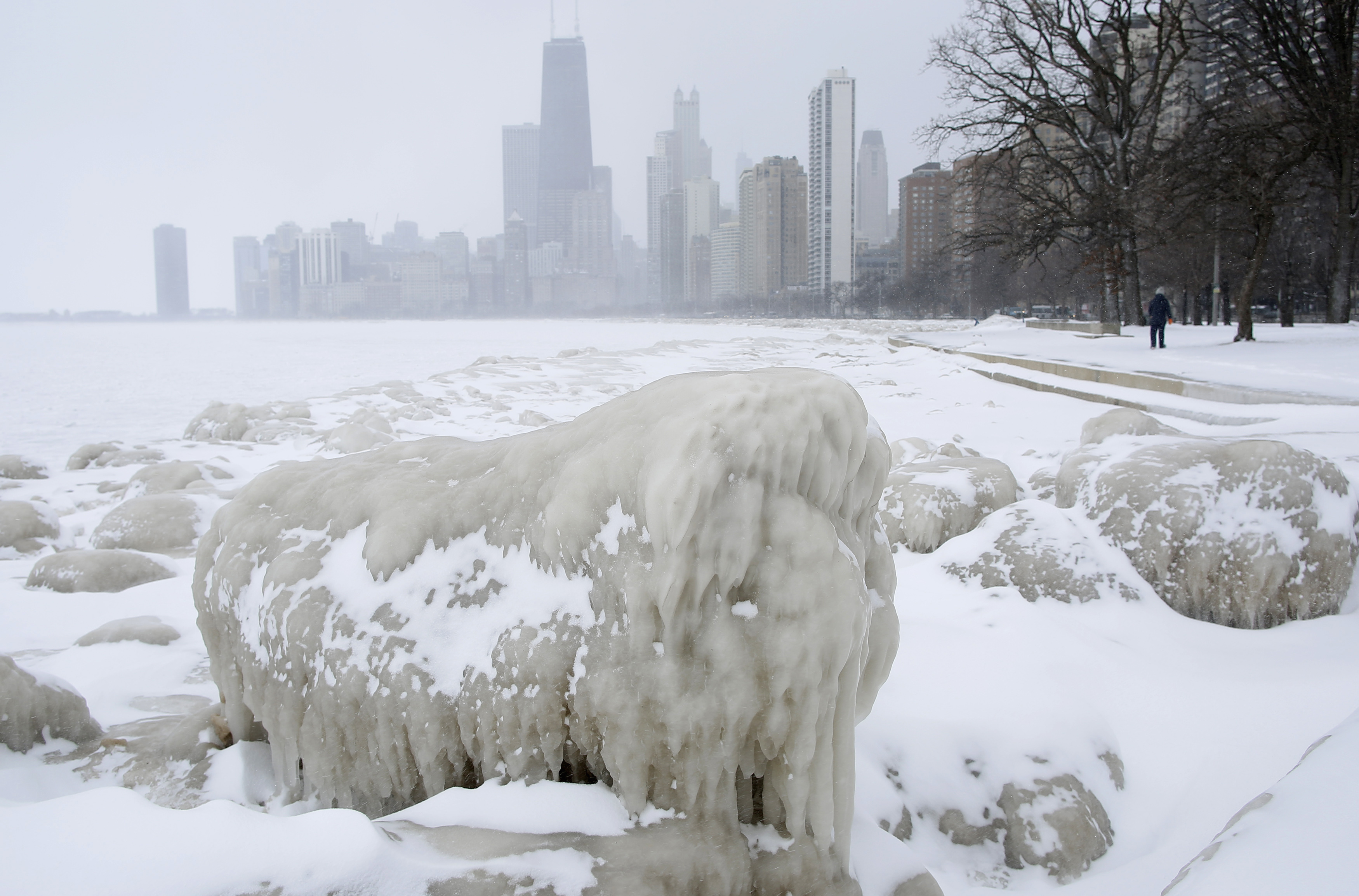A woman walks along a path past mounds of snow and ice along Lake Michigan in Chicago, Illinois, February 26, 2015.  This February was the coldest on record for many cities across the US. Photo by Jim Young/REUTERS.