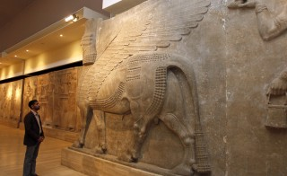 A man looks at ancient Assyrian human-headed winged bull statues at the Iraqi National Museum in Baghdad on Feb. 28, 2015. Photo by Khalid al-Mousily/Reuters