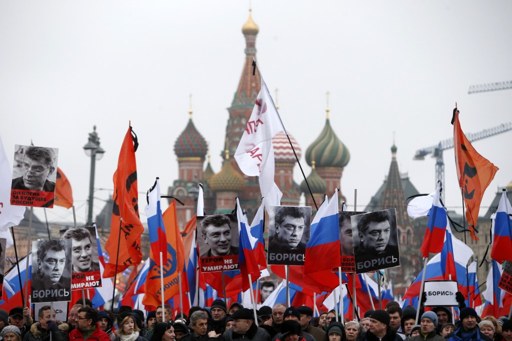 "People hold flags and posters during a march to commemorate Kremlin critic Boris Nemtsov, who was shot dead on Friday night, near St. Basil's Cathedral in central Moscow March 1, 2015. Holding placards declaring ""I am not afraid"", thousands of Russians marched in Moscow on Sunday in memory of Nemtsov, whose murder has widened a split in society that some say could threaten Russia's future.     REUTERS/Sergei Karpukhin (RUSSIA - Tags: CRIME LAW POLITICS CIVIL UNREST TPX IMAGES OF THE DAY) - RTR4RMPB"