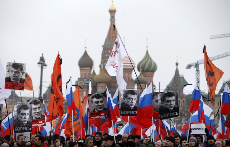 """People hold flags and posters during a march to commemorate Kremlin critic Boris Nemtsov, who was shot dead on Friday night, near St. Basil's Cathedral in central Moscow March 1, 2015. Holding placards declaring """"I am not afraid"""", thousands of Russians marched in Moscow on Sunday in memory of Nemtsov, whose murder has widened a split in society that some say could threaten Russia's future.     REUTERS/Sergei Karpukhin (RUSSIA - Tags: CRIME LAW POLITICS CIVIL UNREST TPX IMAGES OF THE DAY) - RTR4RMPB"""
