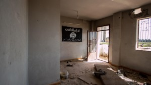An Islamic State flag hangs on the wall of an abandoned building in Tel Hamis in Hasaka countryside after the YPG took control of the area