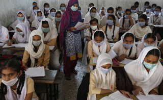 Students and a teacher wear protective masks during a class at a school in the western Indian city of Ahmedabad March 2, 2015. India has seen a sharp rise in the number of swine flu deaths and reported cases this year, prompting officials to investigate the cause and step up efforts to combat the virus. REUTERS/Amit Dave
