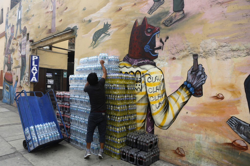 A man carries bottles near a mural in Lima on Mar. 12, 2015.  Credit: Mariana Bazo/REUTERS