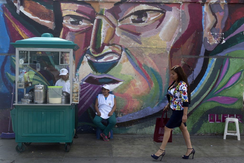A woman walks next to a mural and a food stand in Paseo De La Republica street in Lima on Mar. 12, 2015. Credit: Mariana Bazo /REUTERS
