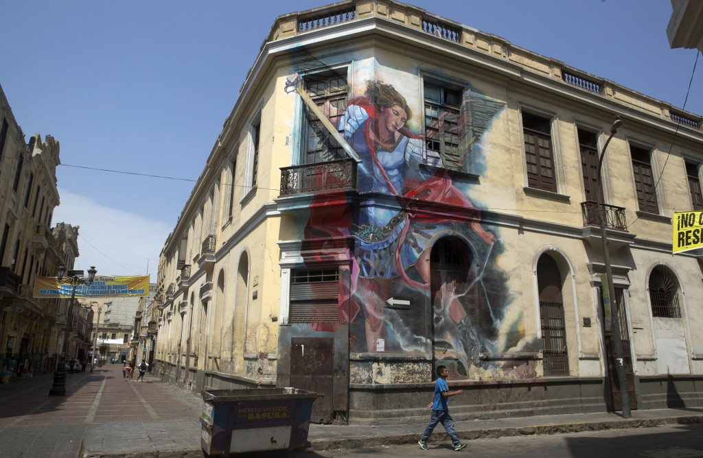 A man walks next to a house with a mural named El Arcangel at Contumaza in Lima on Mar. 12, 2015. Credit:  Mariana Bazo/ REUTERS