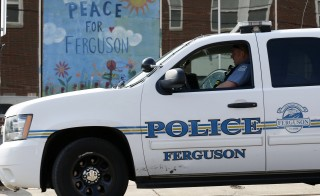 A Ferguson Police officer drives past a mural in Ferguson