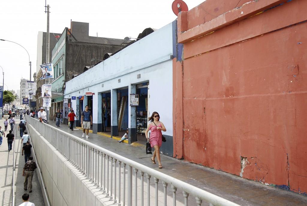 A woman walks past a wall painted to cover a mural at Lampa street in downtown Lima, Mar. 14, 2015. Credit: Enrique Castro-Mendivil/REUTERS.