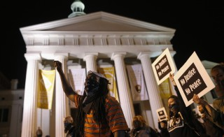 Protesters march in front of the Old Courthouse, as they demonstrate against what they say is police brutality after the Ferguson shooting of Michael Brown, an unarmed black teenager, by a white police officer,  in St. Louis, Missouri, March 14, 2015.  REUTERS/Jim Young  (UNITED STATES - Tags: CRIME LAW CIVIL UNREST POLITICS) - RTR4TDSM