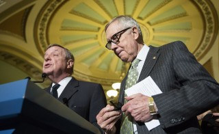 Senate Minority Leader Harry Reid (D-NV) buttons his jacket as Senator Dick Durbin (D-IL) speaks during a press conference on Capitol Hill in Washington on March 17, 2015.      REUTERS/Joshua Roberts