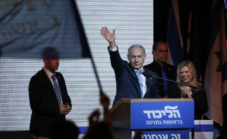Israeli Prime Minister Benjamin Netanyahu waves to supporters beside his wife in Tel Aviv