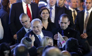Israeli Prime Minister Benjamin Netanyahu (center) greets supporters at party headquarters in Tel Aviv on March 18. Photo by Amir Cohen/Reuters