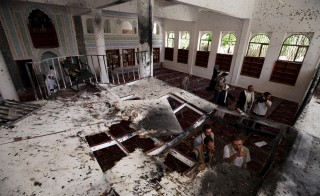 People look inside a damaged mosque after Friday's suicide bomb attack in Sanaa March 22, 2015. Suicide bombers killed at least 137 worshippers and wounded hundreds more during Friday prayers at two mosques in the Yemeni capital Sanaa, in coordinated attacks claimed by Islamic State. Photo by Mohamed al-Sayaghi/Reuters