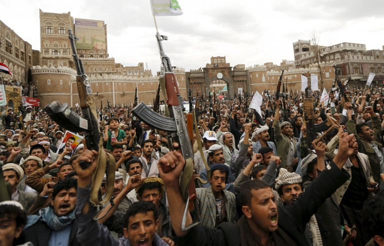 Shi'ite Muslim rebels hold up their weapons during a rally against air strikes in Sanaa