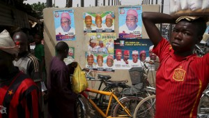 A man carries goods on top of his head at an open market in front of election posters in Kano