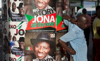 A man stands in front of electoral campaign posters in Lagos