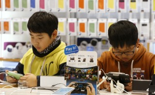 Two young men try out Samsung Galaxy phones at the Samsung Electronics' headquarters in Seoul January 23, 2014. South Korea's education ministry announced a new smartphone app Friday in an effort to prevent student suicides. Photo by Kim Hong-Ji/Reuters