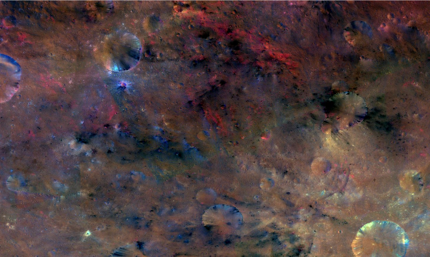 This colorful image from NASA's Dawn mission shows material northwest of the crater Sextilia on the giant asteroid Vesta. While a large asteroid impact probably brought the black material, the red material may have been melted by the impact. Image courtesy of NASA/JPL-Caltech/UCLAMPS/DLR/IDA