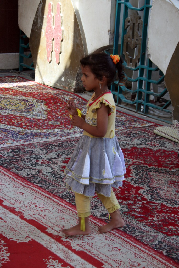 Prayer Rugs A girl waits for her mother to stow their shoes before entering the mosque. Ten percent, or more than 100 million, of the world's Muslims are Shiite. Photo by Larisa Epatko