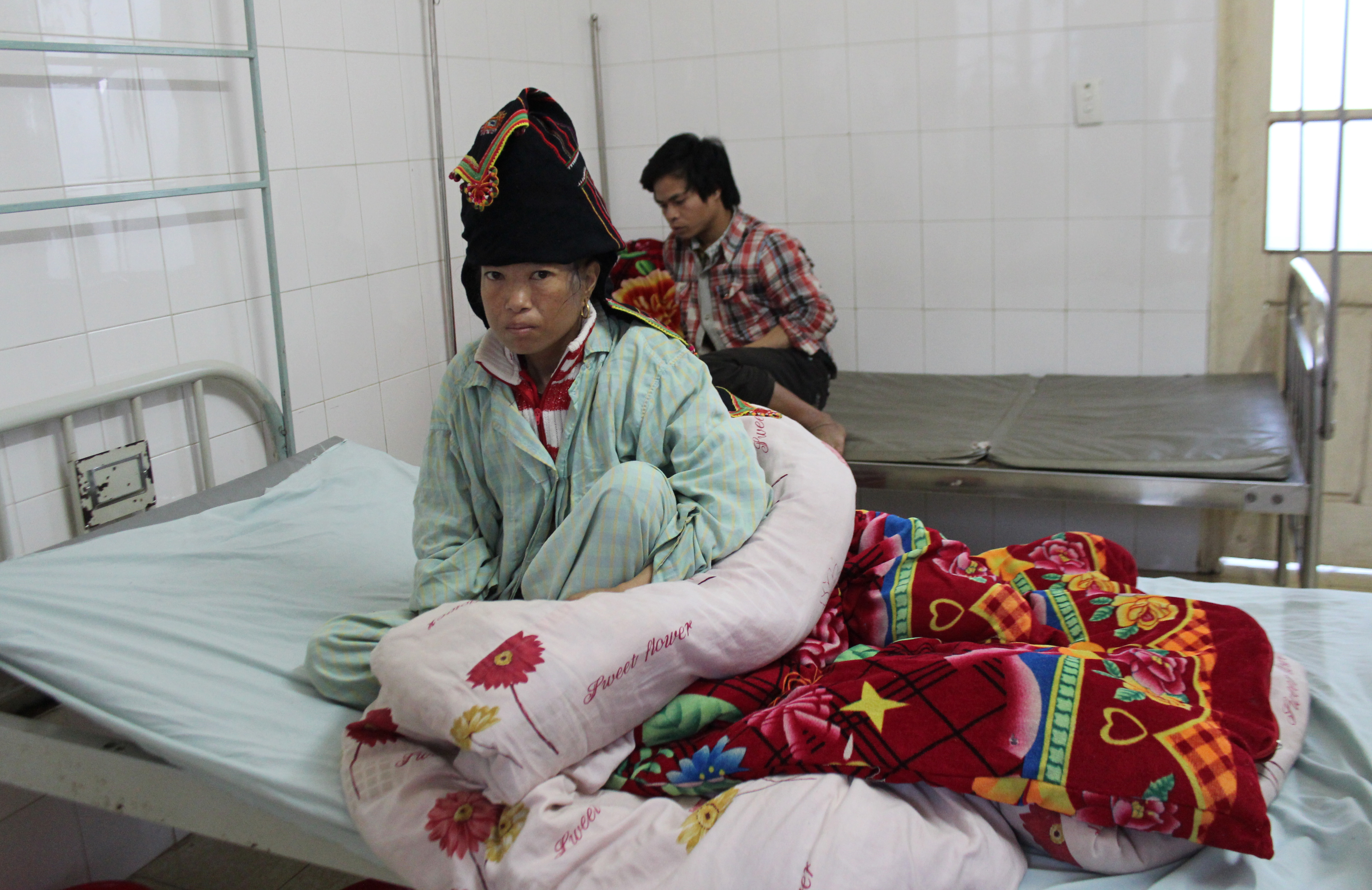 A woman rests as her husband keeps her company in the HIV/AIDS ward at the provincial hospital in Dien Bien Phu City in northwestern Vietnam on Jan. 13, 2015. Photo by Larisa Epatko/PBS NewsHour
