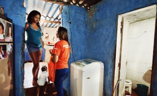 A Mobile Metrix agent asks survey questions of a resident in Rio de Janeiro, Brazil. Photo courtesy of Mobile Metrix